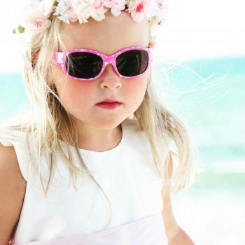 A three year old flower girl wearing an ivory flower girl dress with a pink sash and pink sunglasses.