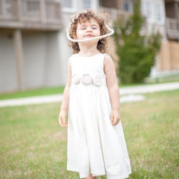 A flower girl standing on a lawn wearing an ivory, cotton flower girl dress with a rosette belt.