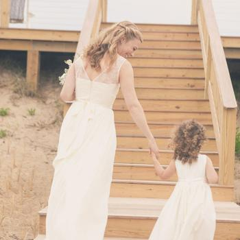 A bride and a young flower girl walking up some steps. The flower girl is wearing an ivory cotton flower girl dress with roses.