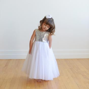A young junior bridesmaid wearing a flower girl dress with a white sequin bodice and a white tulle skirt.
