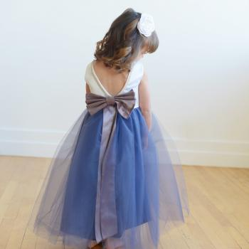 A toddler junior bridesmaid at a wedding wearing a flower girl dress with a purple tulle skirt and a white duchess satin bodice with diamante trim.