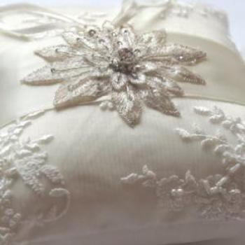 A beaded lace ring cushion with a star flower motif in diamante and ribbon ties.