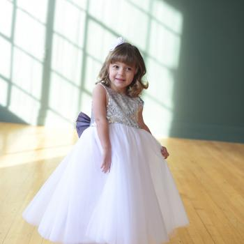 A flower girl at a wedding wearing a silver sequin and tulle flower girl dress with a big bow.