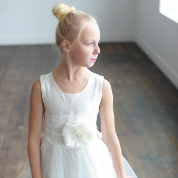 A close up of an 8 year old girl wearing a first communion dress in white with an elasticated belt and flower with a diamanté centre.