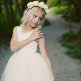 A girl wearing an ivory dress with a tulle skirt and lace bodice with a floral rose head crown
