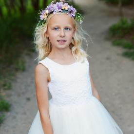 A 7 year old flower girl and junior bridesmaid standing in a field with purple flowers wearing an junior bridesmaid dress and a flower girl headband with purple flowers and yellow flowers.