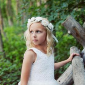 A young flower girl and a girl taking her first communion. The flower girl is wearing a lace flower girl dress with a white flower girl headband and the other girl is wearing a white tulle first communion dress.