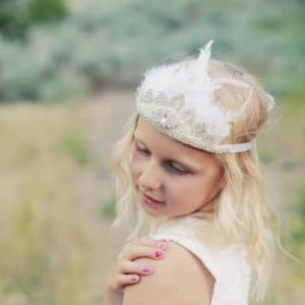 A young girl in a garden wearing an ivory feathered diamanté headband and white flower girl dress with lace bodice.