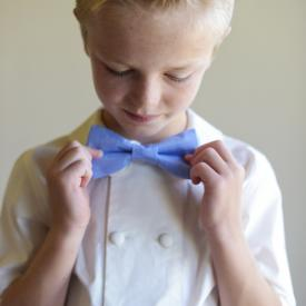 A pageboy waring a baby blue bow tie at a wedding and an ivory pageboy suit.