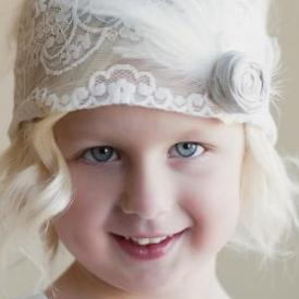 A three year old girl in an elasticated headband with a grey flower motif and feather at the side.