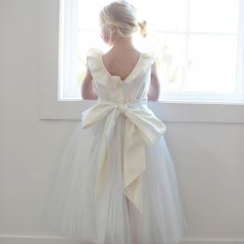 A photo of a junior bridesmaid showing the back of an ivory flower girl dress with a V back and ruffle neckline. The dress has a tulle skirt and sash with a big bow.