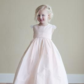 A five year old flower girl in a blush pink flower girl dress in pure wild silk with lace sleeves and silk sash.