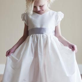 A 7 year old girl wearing a white first communion dress with a v necking and puff sleeves.