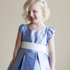 A toddler flower girl wearing a blue silk flower girl dress with puff sleeves and a big white sash and bow