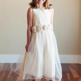 A junior bridesmaid and a flower girl wearing a junior bridesmaid dress with a tulle skirt and flowers on the waist.