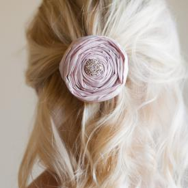 A flower girl wearing a pure silk rolled rosette with a diamante centre in her hair as a hair accessory for a wedding