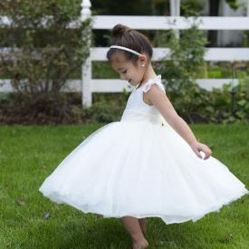 A young toddler girl wearing an ivory flower girl dress with lace sleeves, tulle skirt and ribbon sash.