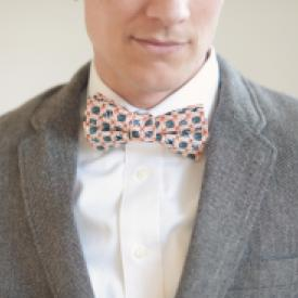 Close up of a groom wearing a tweed jacket and a vintage style salmon pink and b=navy bowtie for a wedding.