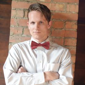 A man leaning on a wall wearing a red silk bow tie.