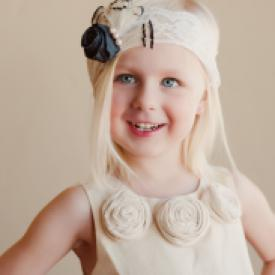 A toddler at a wedding in a church wearing a ivory lace headband with a black flower and black and ivory feathers