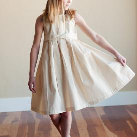 A junior bridesmaid wearing a knee length junior bridesmaid dress in ivory cotton with a rosette flower on the shoulder.