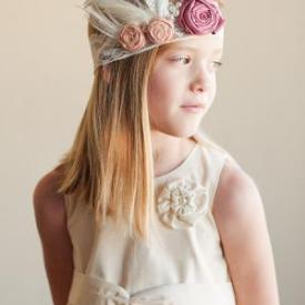 A junior bridesmaid wearing a 1920s Gatsby style dress and a handmade lace headband with feathers and dusky pink and blush pink silk flowers and feathers.