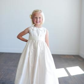A toddler flower girl wearing a pure silk flower girl dress with a Peter Pan collar in ivory , pink, blue, purple and green. The dress has a wide sash which ties in a big bow at the back and come in ballerina length, mid calf or ankle length