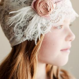 A lace flower girl headband with a beautiful pink silk flower, feathers and pearls
