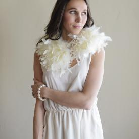 The side view of a bride and a bridesmaid at a wedding wearing an ivory feather collar over a wedding dress.