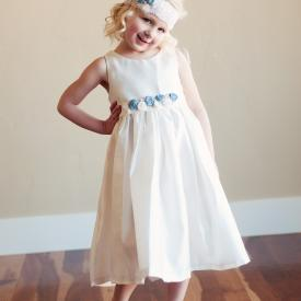 A toddler flower girl wearing a cotton dress with blue and white flowers and pearls