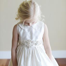 A toddler flower girl and a junior bridesmaid wearing a white flower girl dress and an ivory junior bridesmaid dress. The sash has a beautiful, delicate diamante motif  and the dress has a peter pan collar.