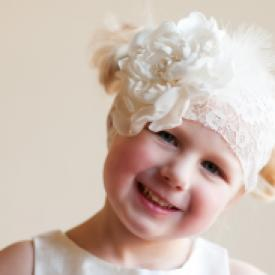 A flower girl wearing an ivory lace headband with oversized peony flower with pearls and feathers.