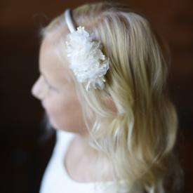 An ivory and white flower girl headband on a satin Alice band. The flowers sit on the left side of the head.