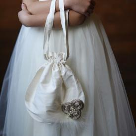 A girl holding a pure silk white flower girl purse for weddings and first communions.