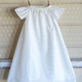 An antique white handmade christening robe in embroidery anglaise with a pretty ribbon flower.
