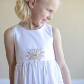 A close up of a girl wearing a white cotton flower girl and first communion dress with a star diamanté motif.