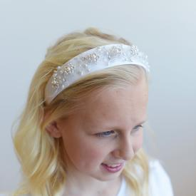 An 8 year old girl wearing a beaded satin first communion headband and a flower girl dress with puff sleeves and a lace hem.