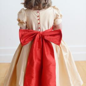 The back of a toddler wearing a flower girl dress in pure silk. The dress is made in gold silk and has a red sash and matching red buttons.
