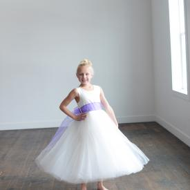 A young flower girl standing on a wooden floor wearing a white silk and tulle flower girl dress with a purple organza sash