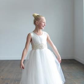 A girl at a wedding in a ballet pose wearing a white First Communion dress or flower girl dress with a diamanté sash and full tulle skirt.