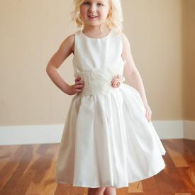 A young flower girl wearing a lace cotton and silk flower girl dress, christening gown or first communion dress with lace sash and flower detail.