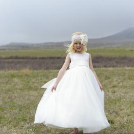 A flower girl wearing a floor length sequin flower girl dress with full silk sash and rhinestone motif with a peter pan collar