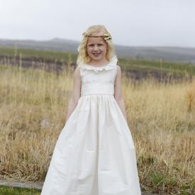 A girl standing in a field with a white silk flower girl dress which has a ruffle collar and a full silk skirt made in the UK.