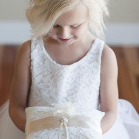 A young flower girl holding a white lace and satin wedding ring cushion with flowers and diamanté accents. It has ribbons to hold the wedding rings.