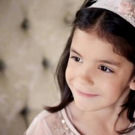 A girl wearing an ivory elasticated flower girl lace headband with pink flowers and a feather an pearl trim