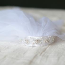 A close up of a white first communion head piece with a veil and a pretty beaded headband.