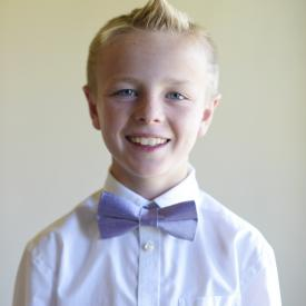 A boy at a wedding wearing a pre-tied pageboys bow tie in lilac silk