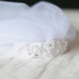 A close up of a first communion veil in white with a double veil and a hand beaded headband.