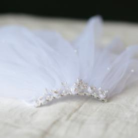 A close up of a first communion tiara with a pearl beaded feature and a double tulle veil.