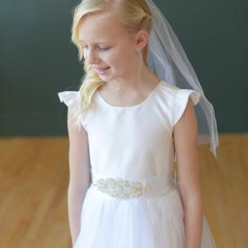 A girl wearing a white silk First Communion dress with butterfly sleeves, a round neckline and a communion veil.